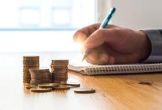 Bemannen Sie die Zählung von Ausgaben, von Budget und von Einsparungen und das Schreiben von Anmerkungen Stockfoto