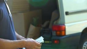 Bemannen Sie die Zählung von Banknoten und das Schließen von van door, Kleinbetrieb, Umzugsunternehmen lizenzfreies stockfoto