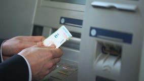 Bemannen Sie die Zählung von den Euros, die von ATM zurückgenommen werden und setzen einlösen Geldbörse, Bequemlichkeit stock footage