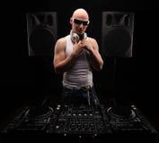 Bemannen Sie DJ in der weißen Hemdspielmusik auf einem DJ-` s Mischer Schönes Tanzen der jungen Frau der Paare Dunkler Hintergrun lizenzfreie stockfotografie