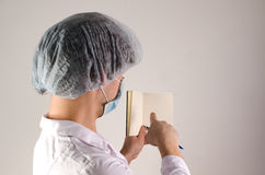 Bemannen Sie Doktor, der Briefpapier hält und zeigen Sie blanck Seite mit dem Finger auf neutralem Hintergrund MEDIZINISCHES Konz Stockbild