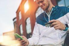 Bemannen Sie draußen sitzen mit Kreditkarte und Handy, Onlinebanking und on-line-Einkaufen Lizenzfreie Stockfotos