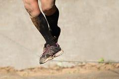 Bemannen Sie ein Drahtseil am Schlammrennen gehen Stockfoto