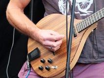 Bemannen Sie eine kundenspezifische E-Gitarre im Abschluss oben spielen Stockfotos