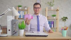 Bemannen Sie in einem Hemd, das im Büro sitzt und wirft eine Münze in das Sparschwein stock footage