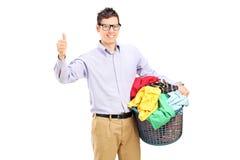 Bemannen Sie einen Wäschekorb hochhalten und Daumen geben Stockfoto