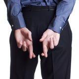 Bemannen Sie Einfluss und verstecken Sie auf seiner Rückseite seine Querfinger Stockfoto