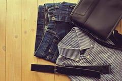 Bemannen Sie Einzelteile, Kleidungsebene auf hölzernem Hintergrund Stockfoto