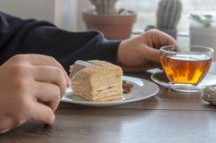 Bemannen Sie Essen einer Tasse Tee mit einem Kuchen Lizenzfreie Stockbilder