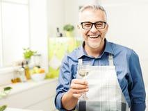 Bemannen Sie Essen eines Glases Weins in der Küche lizenzfreie stockfotografie