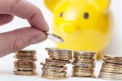 Bemannen Sie Euromünzen gelbem piggy b in der Hand und auf zählen Stockfoto