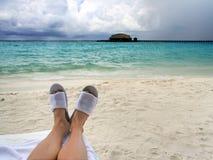 Bemannen Sie Füße in den Strandpantoffeln auf einem Hintergrund des schönen Meeres Lizenzfreies Stockfoto