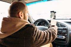 Bemannen Sie Fahrer im Auto, das eigenhändig Smartphoneschirm mit AnwendungsNavigationsanlage berührt Stockbilder