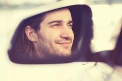 Bemannen Sie Fahrerreflexion im Seitenansichtspiegel des Autos lizenzfreie stockfotos
