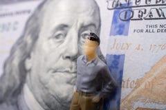 Bemannen Sie Figürchen neben der Banknote von US-Dollar Lizenzfreie Stockfotos
