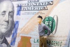 Bemannen Sie Figürchen neben der Banknote von US-Dollar Lizenzfreies Stockfoto