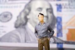 Bemannen Sie Figürchen neben der Banknote von US-Dollar Lizenzfreie Stockfotografie