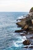 Bemannen Sie Fischen auf den Felsen entlang dem Bondi zu Küstenweg Coogee in Sydney, Australien Lizenzfreie Stockfotos