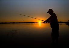 Bemannen Sie Fischen auf einem See vom Boot bei Sonnenuntergang Lizenzfreie Stockfotos