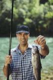 Bemannen Sie Fischen auf Fluss und Vertretungsfischen zur Kamera lizenzfreies stockfoto