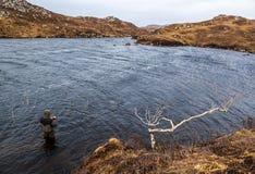Bemannen Sie Fischen für Forelle und Lachse in einem schottischen Loch stockfotos
