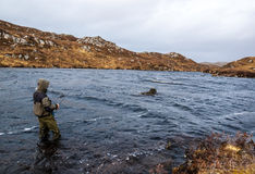 Bemannen Sie Fischen für Forelle und Lachse in einem schottischen Loch lizenzfreie stockfotografie