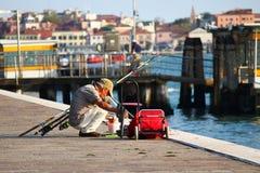 Bemannen Sie Fischen von der Seeseite nahe Docks in Venedig Stockbilder