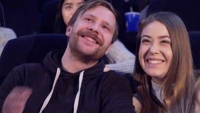 Bemannen Sie Flüstern etwas zu seiner Freundin am Kino stock video