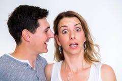 Bemannen Sie Flüstern im Ohr seiner Freundin stockfotografie