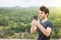 Bemannen Sie Fotos mit seinem Telefon in einer Westlandschaft glücklich machen Lizenzfreie Stockfotografie