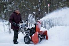 Bemannen Sie funktionierende Schneefräse an einem stürmischen Winter ` s Tag Stockbild