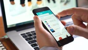 Bemannen Sie Gebrauch iphone, um zu kaufen on-line--Amazonas-APP auf dem Schirm stock footage