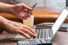 Bemannen Sie Gebrauchskreditkarte, um Produkt auf Laptop zu kaufen lizenzfreies stockbild