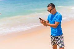 Bemannen Sie Gebrauchstelefon auf dem schreibenden Strand oder benutzen Sie Internet am sonnigen Tag Lizenzfreie Stockfotografie