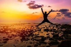 bemannen Sie glücklichen Sprung mit seinen Händen oben während des Sonnenuntergangs am Strand lizenzfreies stockbild