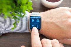 Bemannen Sie Hände in der Uhr mit intelligentem Haus des Programms auf Schirm Stockbild