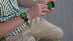 Bemannen Sie Hände unter Verwendung des grünen Schlüssels des Smartphone und der intelligenten Uhren stock footage