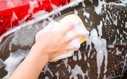 Bemannen Sie Händewaschen Brown-Auto mit gelbem Schwamm und Blasen Lizenzfreie Stockfotografie