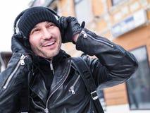 Bemannen Sie hörende Musik über Kopfhörer in Brooklyn, New York Winter Er hat glückliches Lächeln Stockfotos