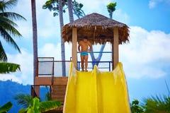 Bemannen Sie Haben des Spaßes auf Wasserrutschen im tropischen Aquapark Stockbilder