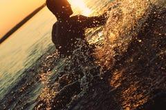 Bemannen Sie Haben des Spaßes im Wasser bei Sonnenuntergang Lizenzfreies Stockbild