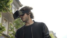 Bemannen Sie Haben des Spaßes mit den Gläsern der virtuellen Realität, die in der Stadt im Freien sind, die durch vr Erfahrung üb stock video footage