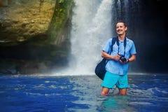 Bemannen Sie Haben einer abenteuerlichen Spurhaltung mit Kamera nahe dem Wasserfall Stockbild