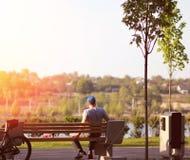 Bemannen Sie Haben einer Kaffeepause auf einer Bank im Park, malerische Ansicht, Sonnenuntergang Lizenzfreie Stockbilder