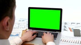 Bemannen Sie Hand auf Laptoptastatur mit grünem Schirm stock video