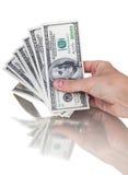 Bemannen Sie Hand mit 100 Dollarscheinen, die auf einem weißen Hintergrund lokalisiert werden Lizenzfreies Stockbild
