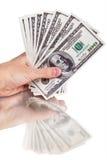 Bemannen Sie Hand mit 100 Dollarscheinen, die auf einem weißen Hintergrund lokalisiert werden Stockfotografie