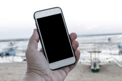 Bemannen Sie Hand mit Smartphone mit leerem Raum auf einem Strandhintergrund, Bali Stockfoto