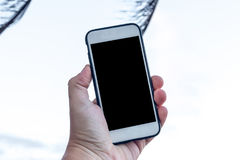 Bemannen Sie Hand mit Smartphone mit leerem Raum auf einem Strandhintergrund, Bali Stockfotos