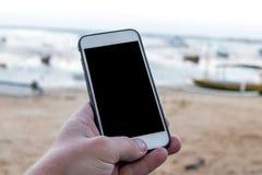 Bemannen Sie Hand mit Smartphone mit leerem Raum auf einem Strandhintergrund, Bali Stockbild